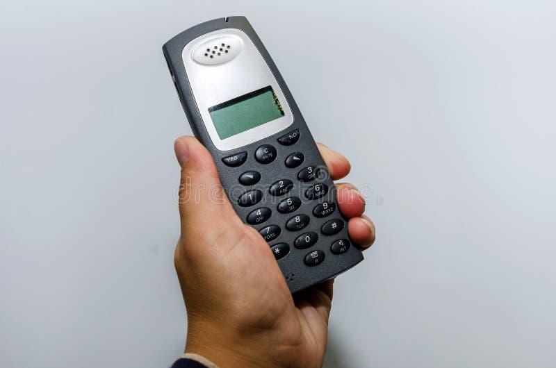 Téléphone sans fil de bureau à disposition sur le fond de mur photo stock