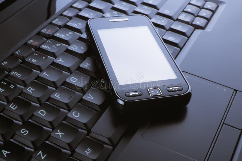 Téléphone sur un ordinateur portatif images stock