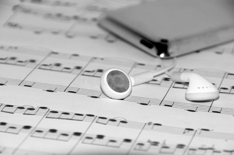 Téléphones d'oreille sur les notes musicales images stock