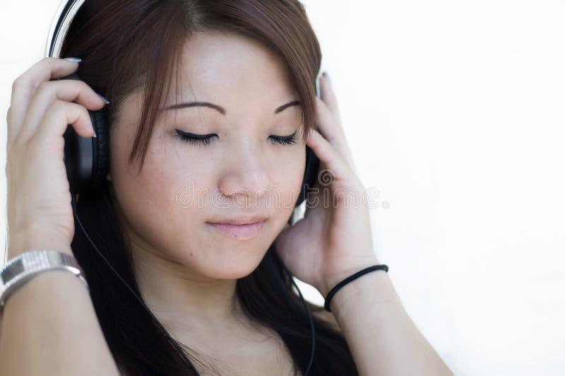 téléphones de écoute principaux de musique à la femme photo libre de droits