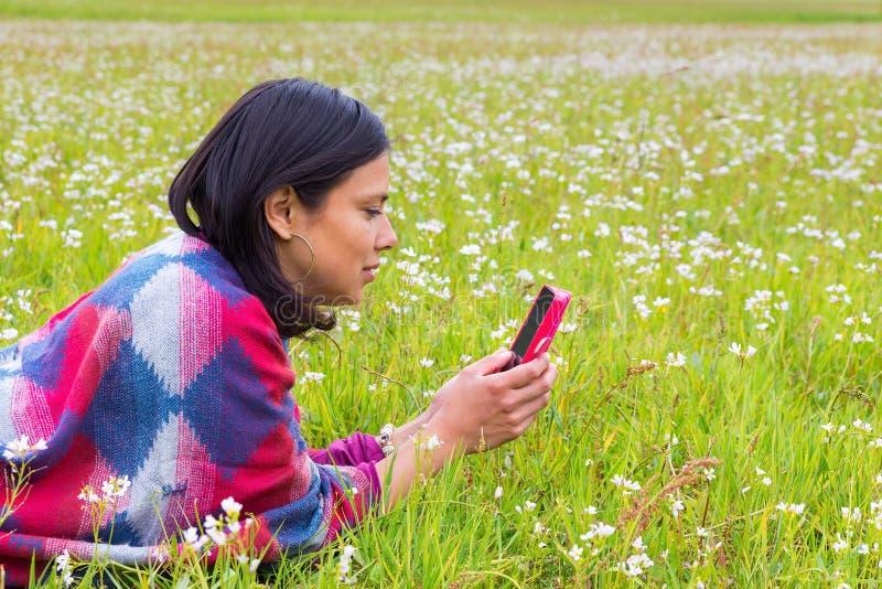 Téléphones menteur de femme dans le pâturage de floraison images stock