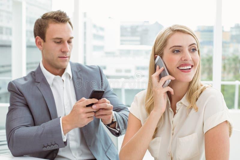 téléphones mobiles de gens d'affaires utilisant image stock