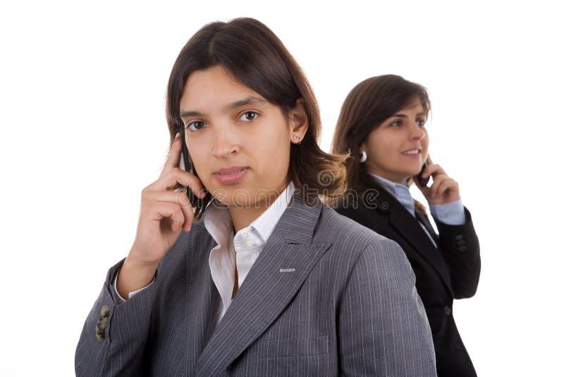 téléphones portables deux de fixation de femme d'affaires image stock