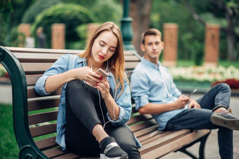 Téléphonez la dépendance, couple de sourire sur le banc en parc images stock