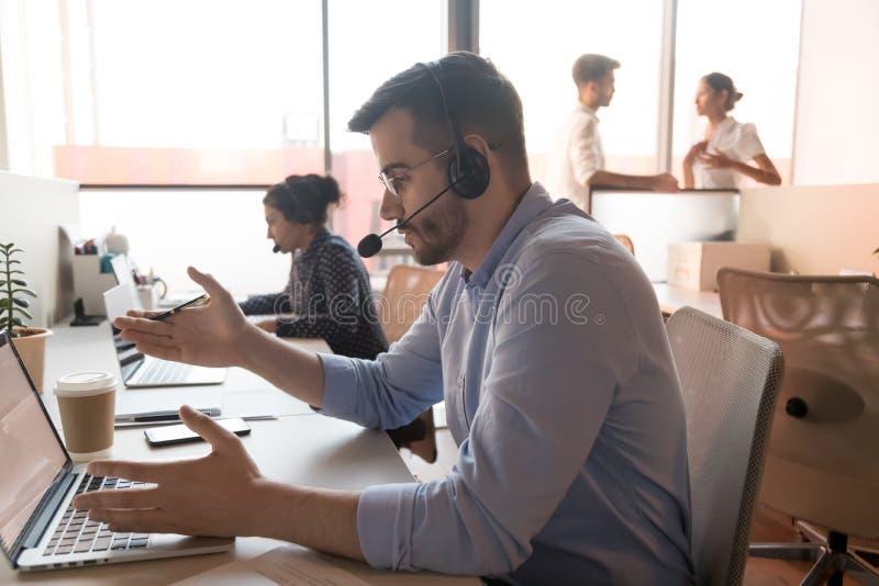 T?l?prospecteur masculin dans le casque consulter le client en ligne image stock