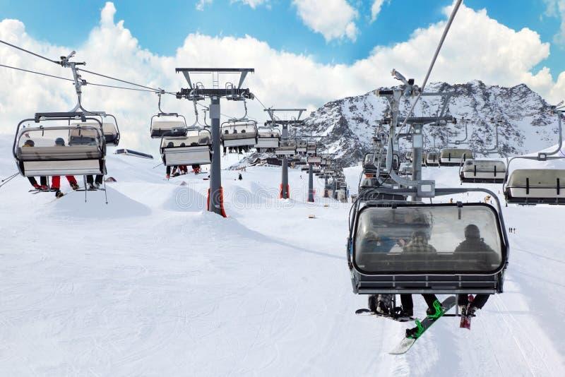 Télésiège de ski avec des skieurs en montagnes image stock