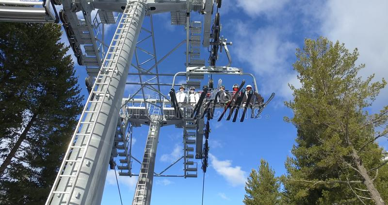 Télésiège de ski avec des skieurs en montagnes couronnées de neige photos stock