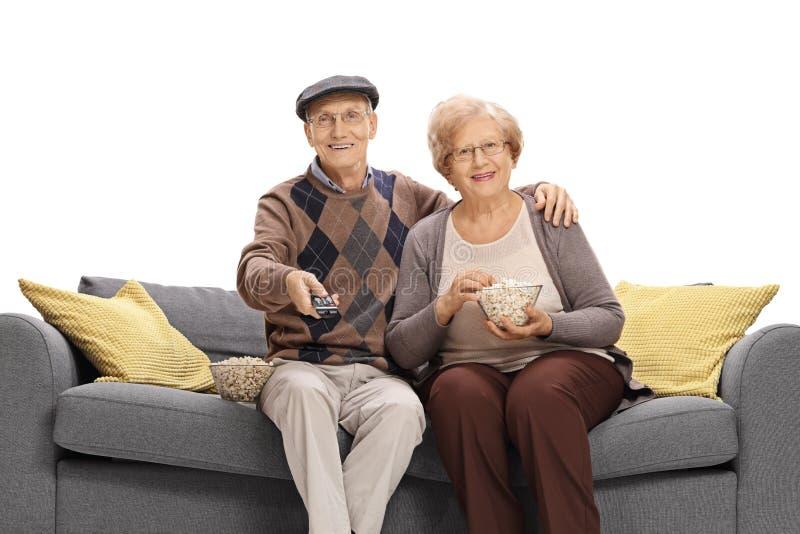 Télévision de couples supérieurs et maïs éclaté de observation de consommation posé sur s photographie stock