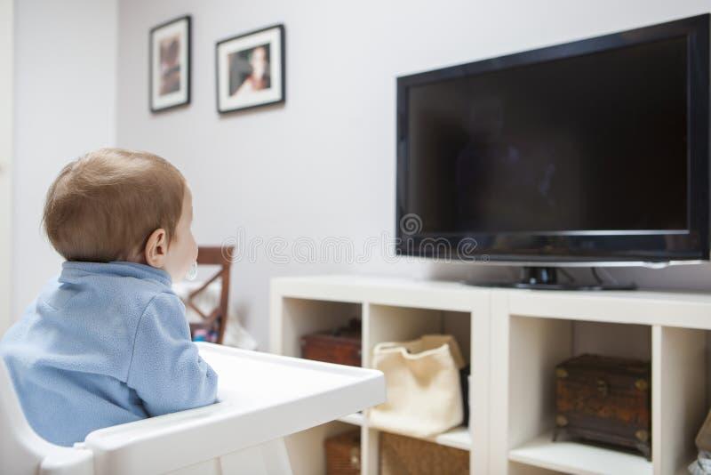 Télévision de observation de bébé garçon dans le salon photos stock