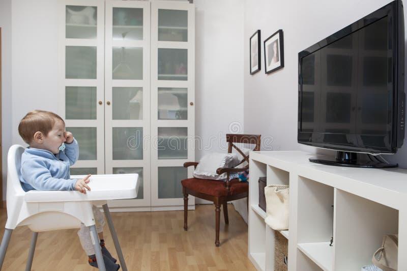 Télévision de observation de bébé garçon somnolent photo stock
