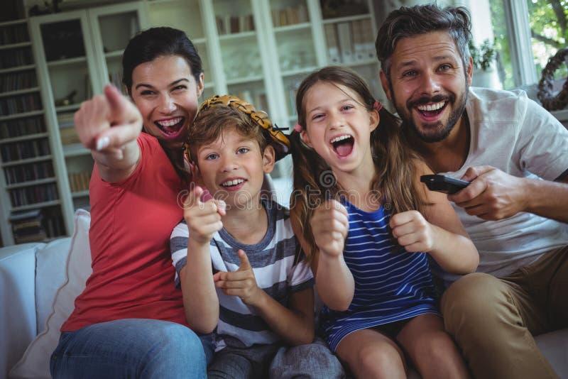 Télévision de observation de famille enthousiaste photos stock