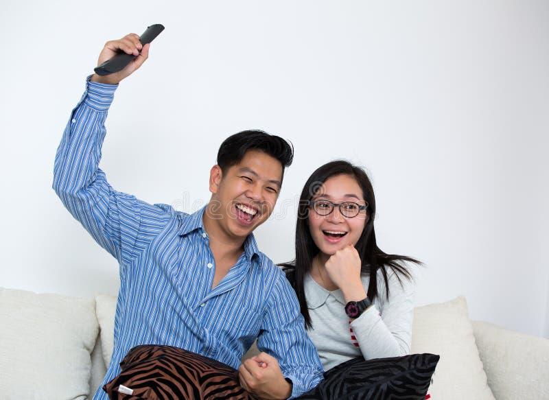 Télévision de observation de jeunes couples à la maison images stock