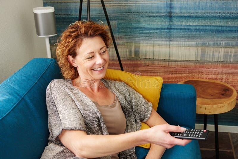 Télévision de observation de sourire de femme avec à télécommande photographie stock libre de droits
