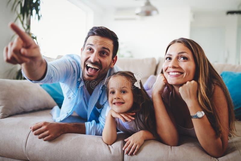 Télévision de observation de famille heureuse à leur maison photographie stock