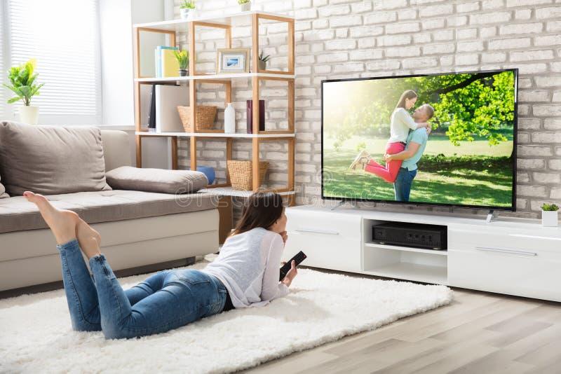 Télévision de observation de femme à la maison photographie stock