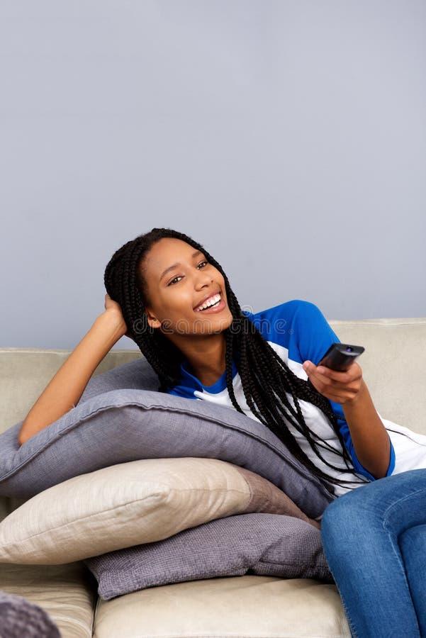 Télévision de observation de jeune femme africaine décontractée à la maison photos stock