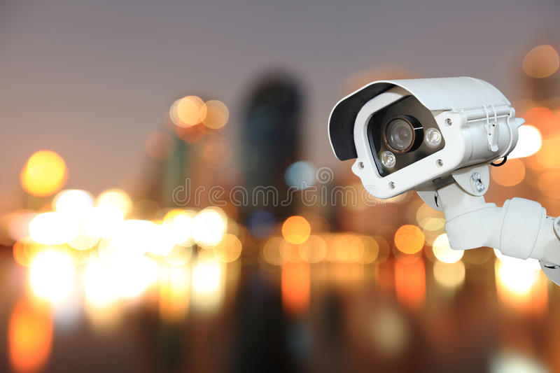 Télévision en circuit fermé avec la ville de flou de bokeh à l'arrière-plan de nuit image stock