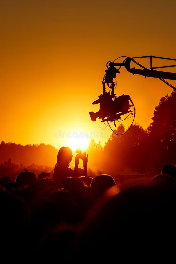 Télévision en direct de caméra vidéo sur l'événement d'été Silhouette, studio extérieur contre le ciel orange images stock