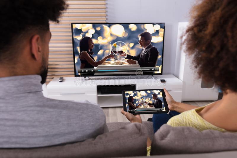 Télévision se reliante de couples par WiFi sur la Tablette de Digital photographie stock