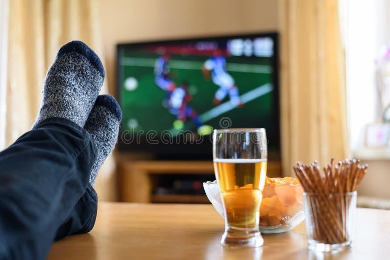 Télévision, TV observant (match de football) avec des pieds sur la table et images stock