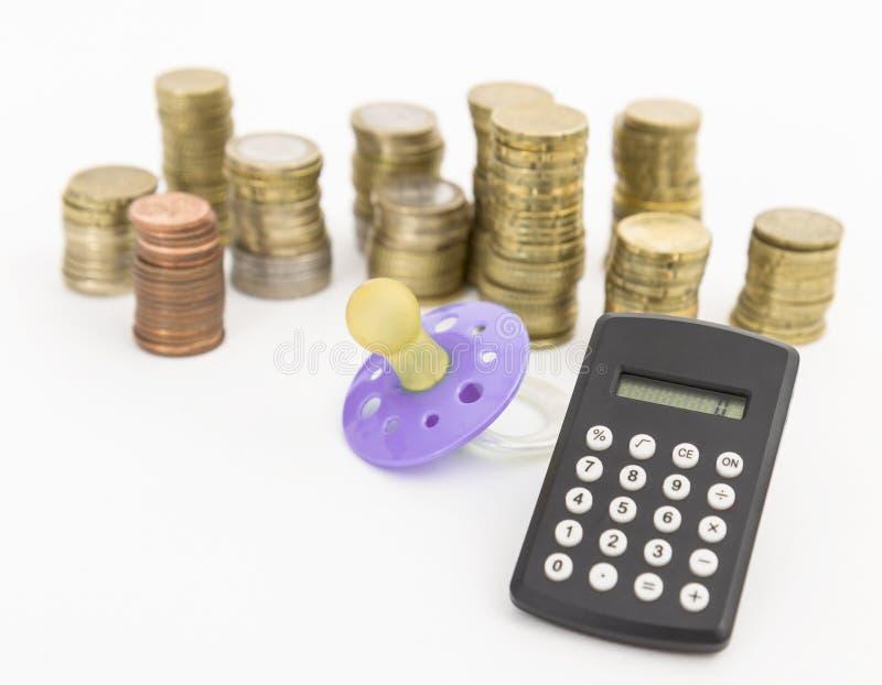 Tétine avec la monnaie métallique et la calculette image libre de droits