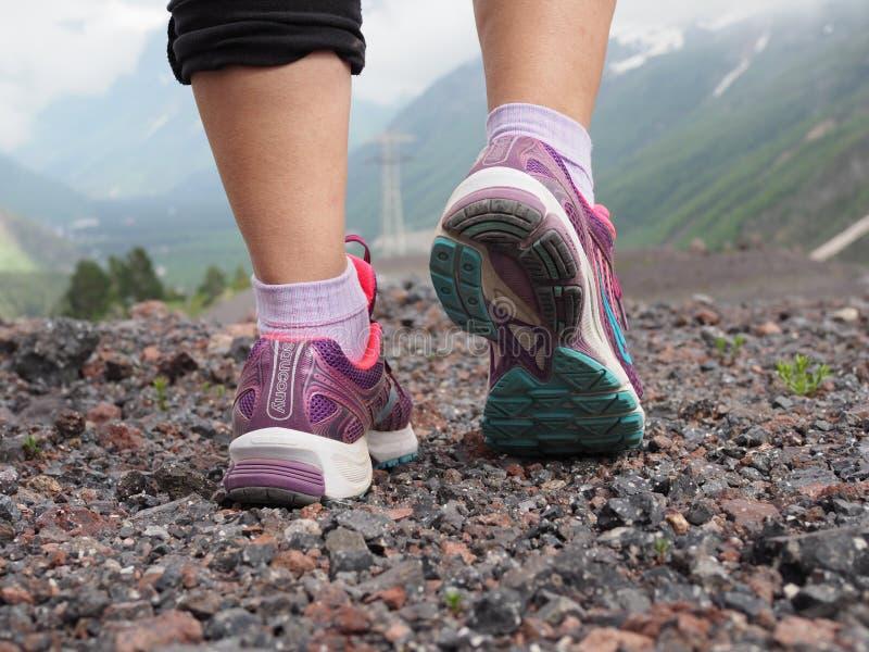 Tênis de corrida do Saucony das mulheres coloridas bonitas, sapatilhas à opinião traseira dos pés das mulheres com as montanhas n fotos de stock