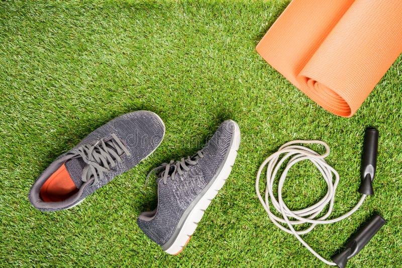 Tênis de corrida e corda de salto para treinar, em um fundo da grama imagens de stock