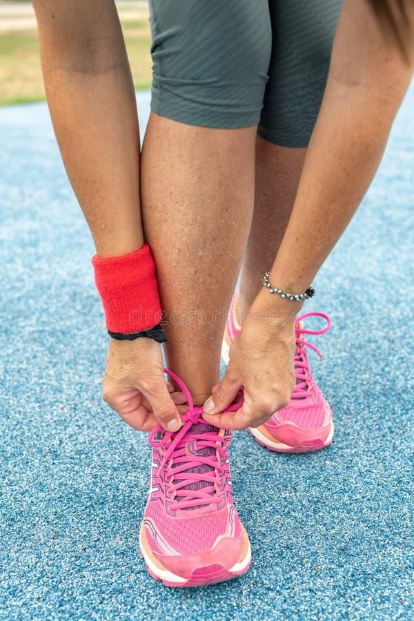 Tênis de corrida - mulher que amarra laços de sapata na trilha da corrida do parque da cidade fotos de stock royalty free