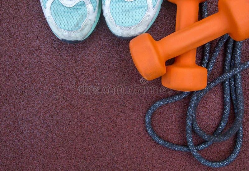 Tênis de corrida, pesos, corda de salto - os acessórios da aptidão em uma borracha dos esportes surgem Copie o espaço para o text fotos de stock