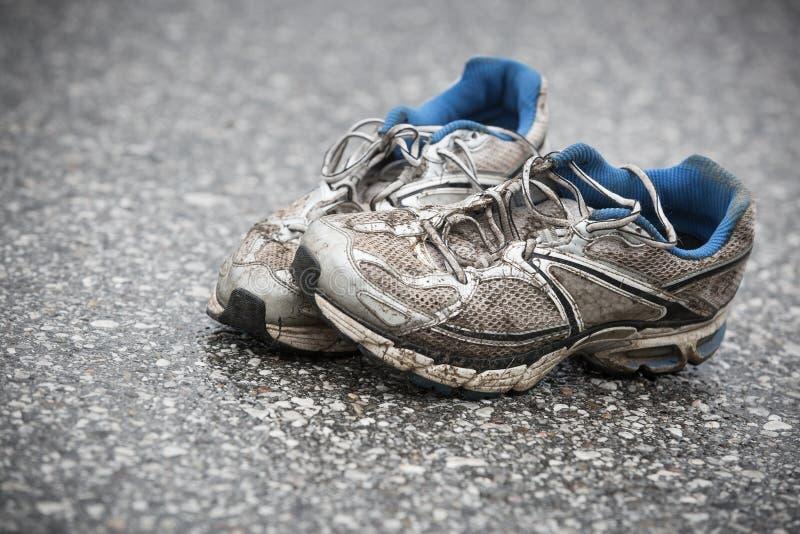 Tênis de corrida vestidos, sujos, fétidos e velhos em uma estrada do alcatrão imagem de stock