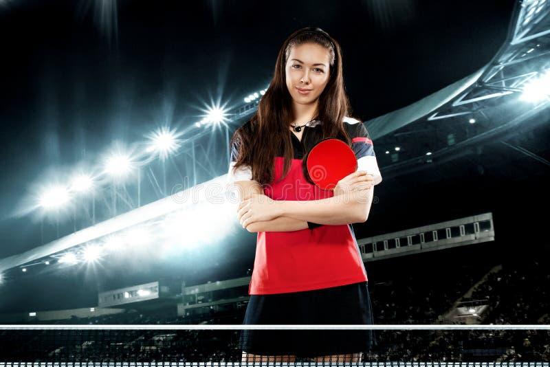 Tênis de mesa consideravelmente desportivo do jogador da menina dos jovens no fundo com luzes fotografia de stock royalty free