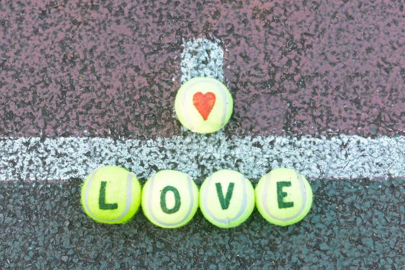 Tênis do amor - a palavra e o coração dão forma tirado em bolas imagem de stock