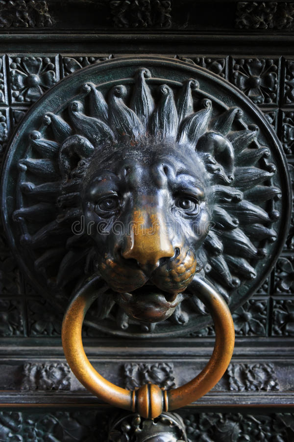 Tête antique de lion en métal sur la porte à l'église catholique image stock