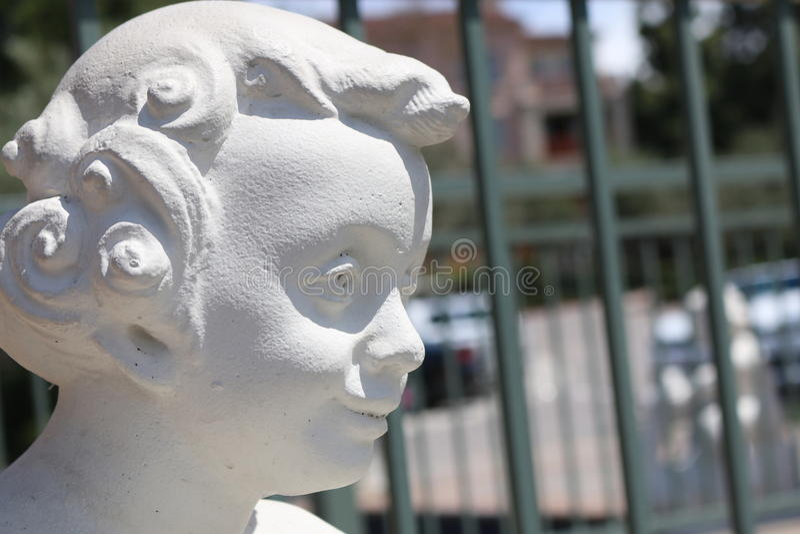 Tête blanche de statue d'enfant heureuse - compensation photographie stock