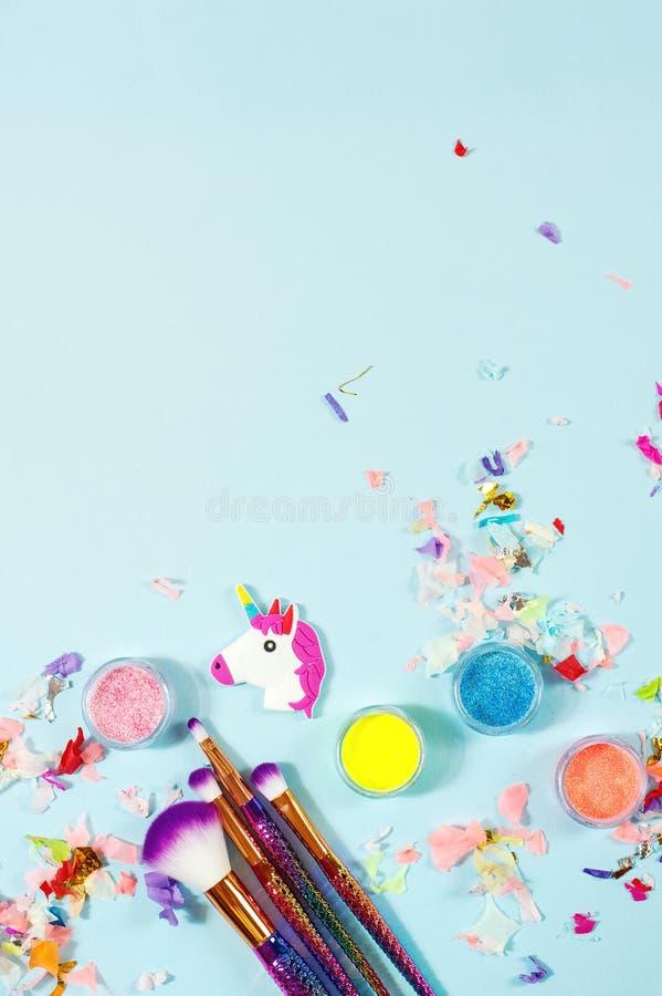 Tête d'une licorne et des fards à paupières de scintillement sur un fond bleu photos stock
