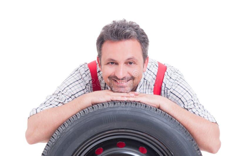 Tête de repos de mécanicien amical sur le pneu photographie stock