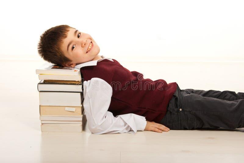 Tête de repos de sourire d'écolier sur des livres images libres de droits
