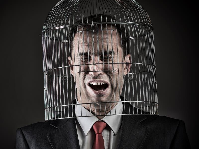 Tête du ` s d'employé de bureau à l'intérieur d'une cage à oiseaux image stock