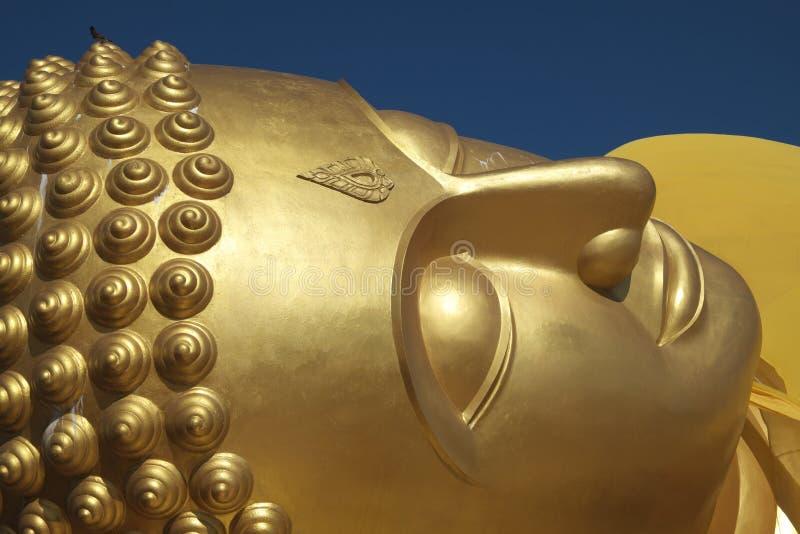 Tête en gros plan de statue étendue de Bouddha dans un temple en Thaïlande images libres de droits