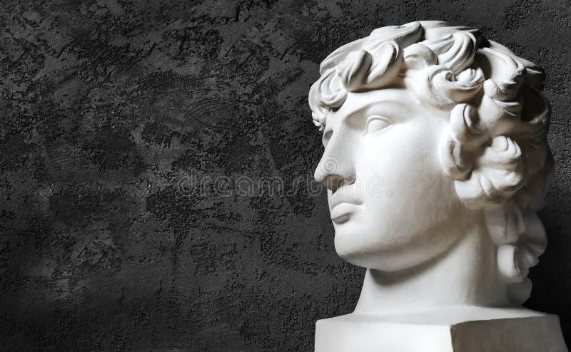 Tête grecque Antinous de plâtre sur un fond foncé images stock