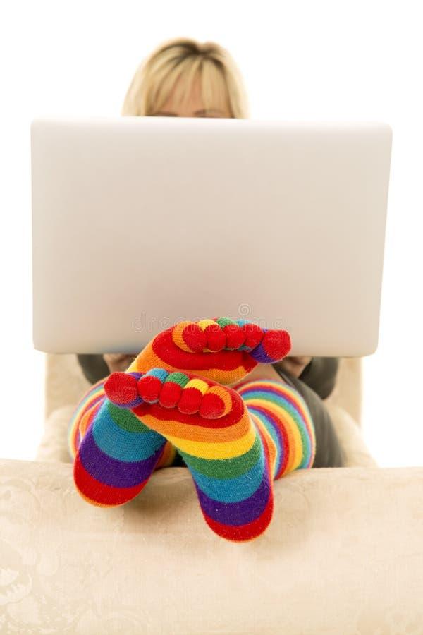 Tête lumineuse de chaussettes de femme derrière l'ordinateur portable photographie stock