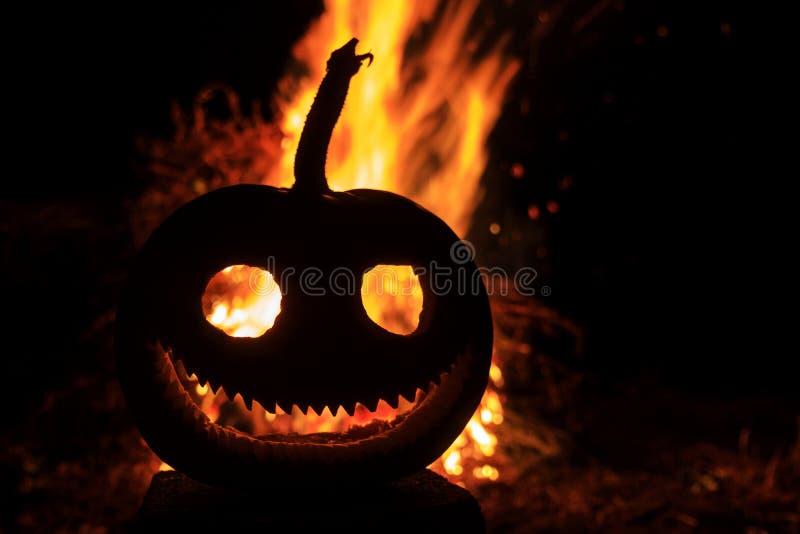 Tête malveillante de potiron de grimace avec un feu à l'arrière-plan photo libre de droits