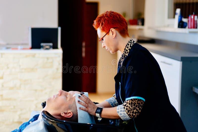 Tête masculine de client de lavage de coiffeur dans le salon de coiffure images libres de droits