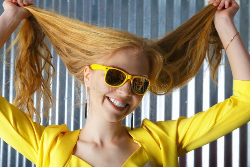 Tête tirée de la femme blonde de sourire dans des lunettes de soleil jouant avec des cheveux photos stock