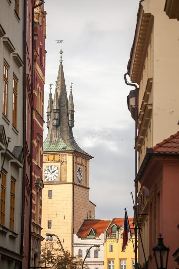 Típica calle estrecha de Stare Mesto, el centro histórico de Praga, República Checa, con un enfoque en el campanario y el reloj imagen de archivo