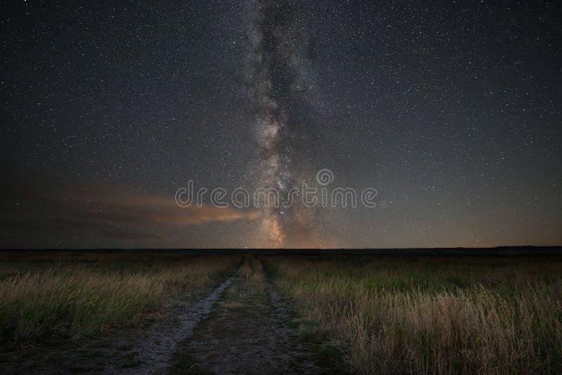 Título del camino de tierra hacia la galaxia de la vía láctea imagenes de archivo