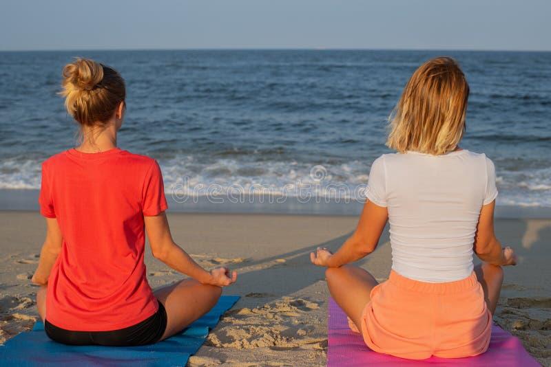 Título: Jovens mulheres que praticam a ioga na praia no por do sol Meditar das meninas, sentando-se na pose dos lótus fotografia de stock