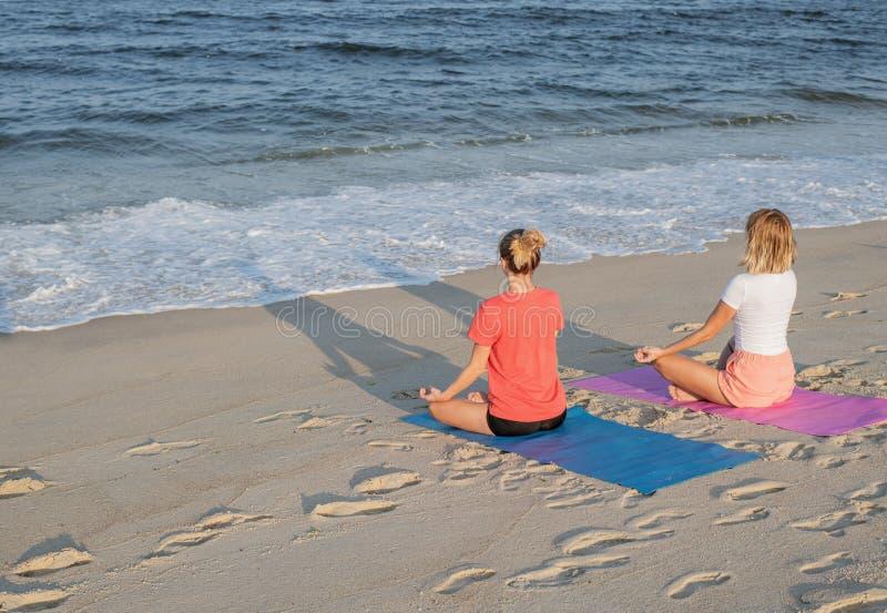 Título: Jovens mulheres que praticam a ioga na praia no por do sol Meditar das meninas, sentando-se na pose dos lótus imagem de stock