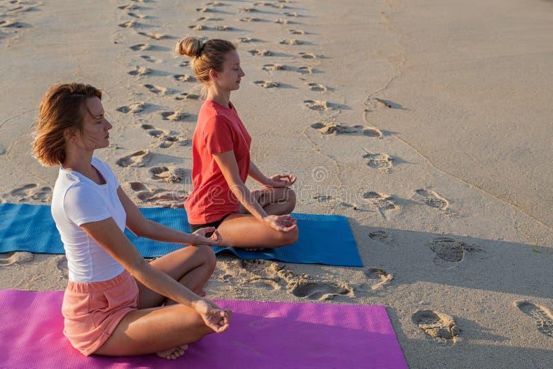 Título: Jovens mulheres que praticam a ioga na praia no por do sol Meditar das meninas, sentando-se na pose dos lótus imagem de stock royalty free