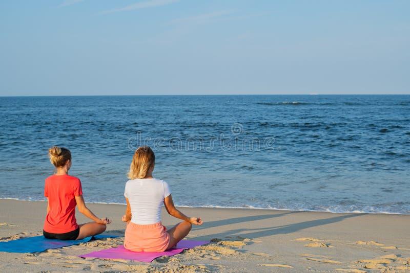 Título: Mujeres jovenes que practican yoga en la playa en la puesta del sol El meditar de las muchachas, sentándose en actitud de imágenes de archivo libres de regalías